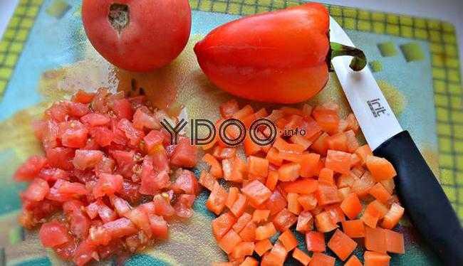 помидор и болгарский перец в целом и нарезанном виде на стеклянной разделочной доске, рядом керамический нож