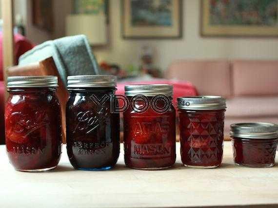пять баночек с солеными сливами на зиму на кухонном столе