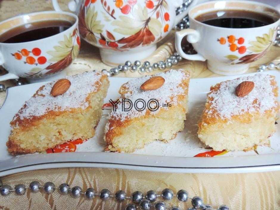 тарелка с тремя кусочками басбусы, украшенной кокосовой стружкой и миндалем, на тарелке, на фоне две чашки с черным чаем, заварник, серебристые бусы