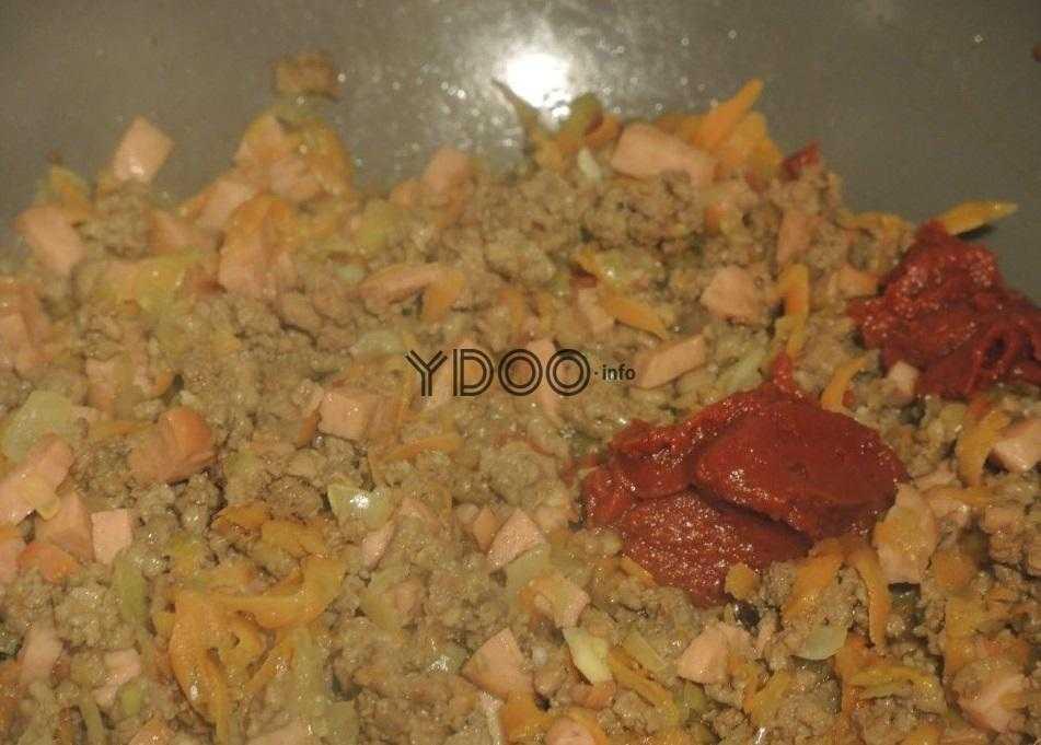 фарш, сосиски, лук и морковь тушеные с томатной пастой на сковороде