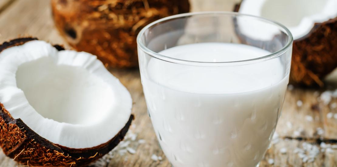 кокосовое молоко в стакане, рядом половинка кокоса