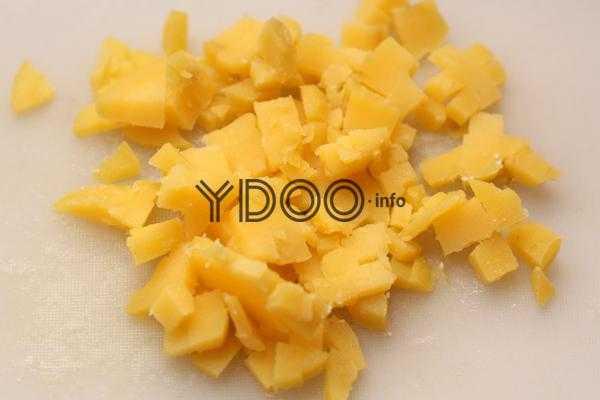 вареная картошка, нарезанная кубиками на разделочной доске