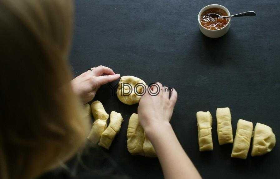 кусочки теста на столе, один из кусочков разминается руками, рядом стоит креманка с абрикосовым джемом, внутри чайная ложка