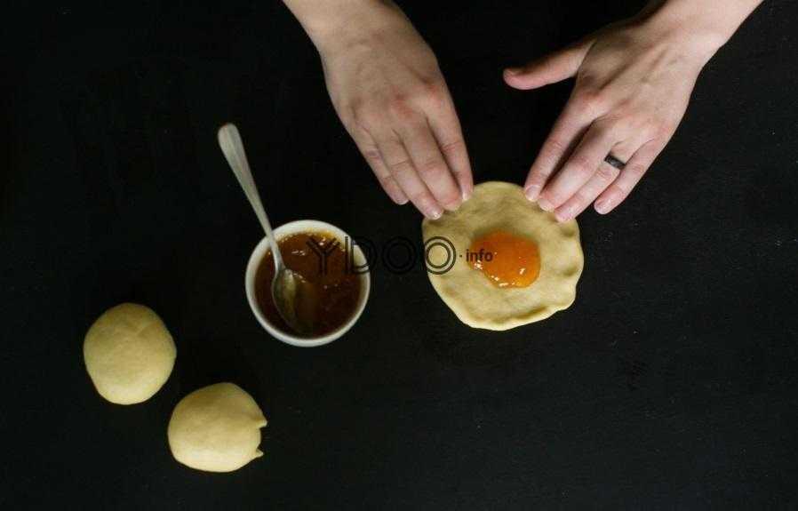 два шарика теста с абрикосовым джемом, рядом креманка с абрикосовым джемом, лепешка из теста, внутри которой джем