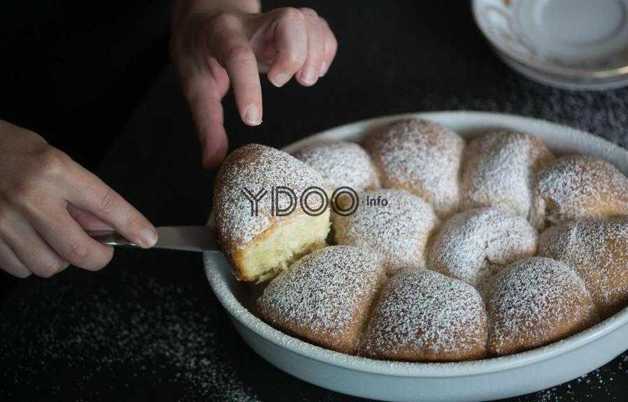 пышные булочки присыпанные сахарной пудрой, в форме для запекания, одну булочку достают лопаткой из формы