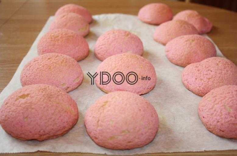 круглые пирожные шу розового цвета на пергаментной бумаге на столе