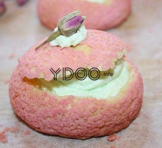 розовое пирожное шу со сливочным кремом зеленого цвета внутри, сверху которого лежит немного крема и маленький бутончик розы