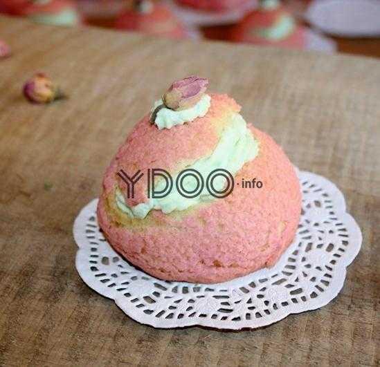 пирожное шу с зеленым сливочным кремом внутри, украшенное маленьким бутоном розы, лежит на ажурной салфетке белого цвета