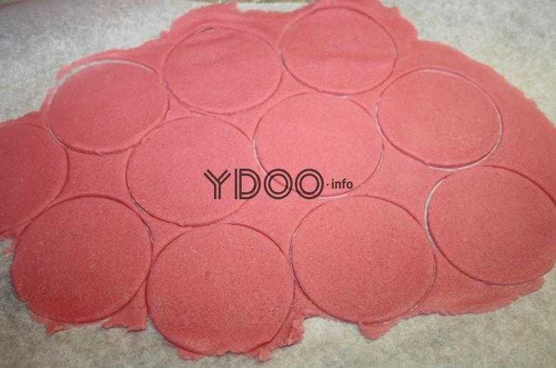 вырезанные кружочки на тонко раскатанном красном тесте