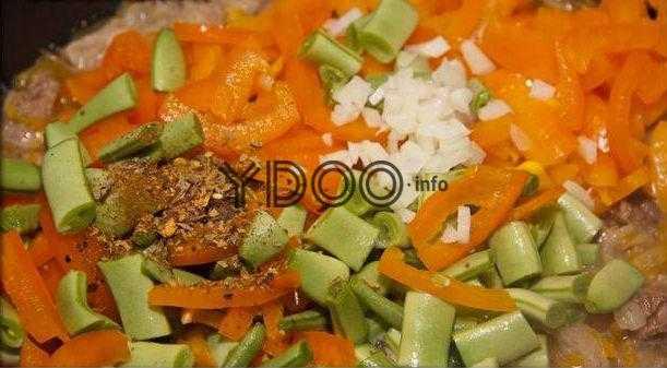 мясо с нарезанным кубиками болгарским перцем, стручковой фасолью, измельченным чесноком на сковороде