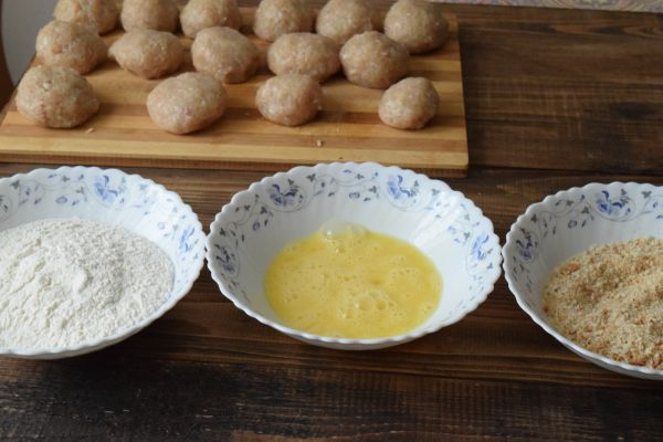 сырые куриные шарики на полосатой деревянной разделочной доске, панировочные сухари, мука и взбитые яйца в трех разных белых тарелках на столе