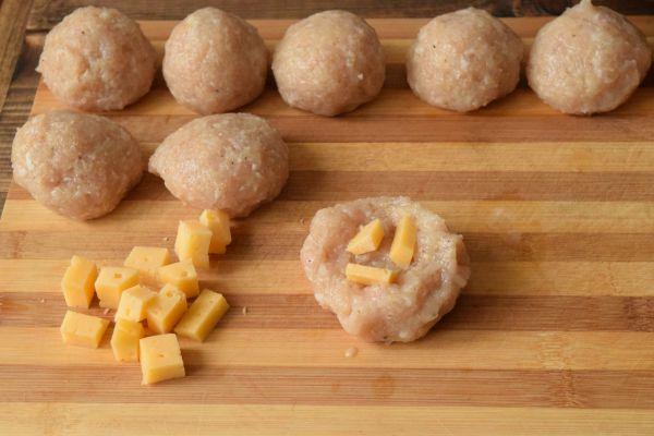 сырые куриные шарики с кусочком твердого сыра внутри на полосатой деревянной разделочной доске