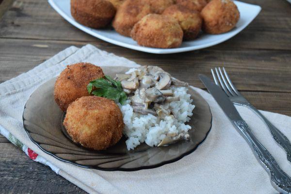 два прожаренные куриные шарики с отварным рисом, кусочками грибов и петрушкой на плоской темной стеклянной тарелке на столе, покрытом полотенцем, рядом вилка и нож