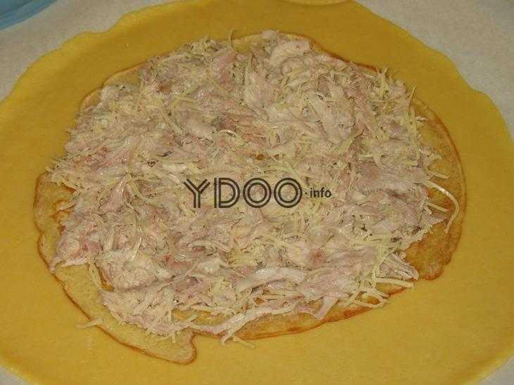 на столе лежит тонкий пласт раскатанного теста, сверху лежат блинчики и начинка из курицы и тертого сыра