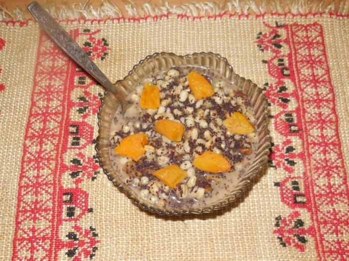 кутья из пшеничной каши, мака и изюма, украшенная кусочками кураги, в стеклянной пиале с ложкой на столе, прикрытом полотенцем