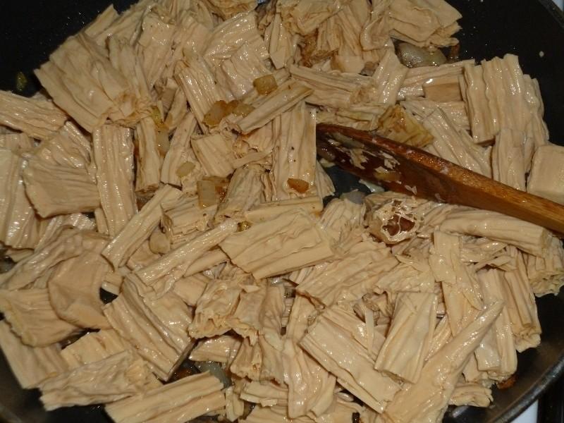 кусочки спаржи, перемешанные с жареным репчатым луком, в сковороде с деревянной лопаткой