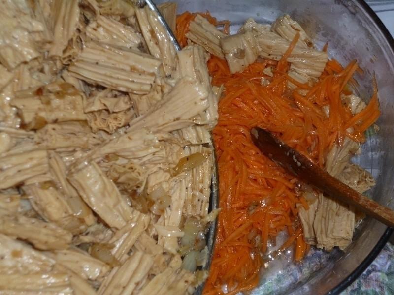 жареная спаржа с луком, перемешанная с тертой морковью, в стеклянной миске с деревянной лопаткой