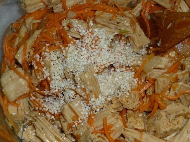 салат из жареной спаржи и тертой моркови, присыпанный кунжутом, в миске с деревянной лопаткой