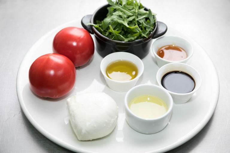 белая тарелка с соусами в маленьких чашечках, маленьким кусочком сыра, помидорами и свежей зеленью