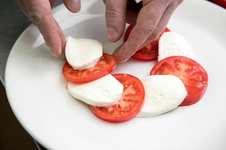 нарезанные кружочками помидоры и сыр, которые выкладывают на тарелку