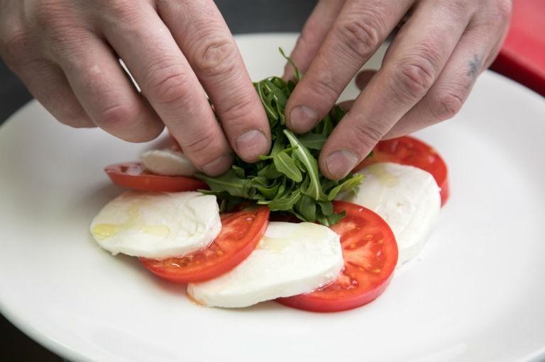 свежую рукколу выкладывают в центр салата из помидоров и сыра на белой тарелке