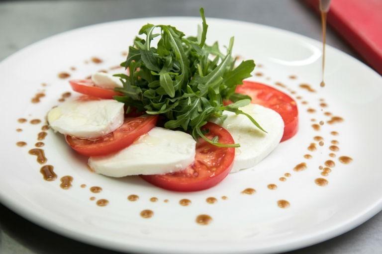 салат из помидоров, сыра и зелени на белой тарелке, политый и украшенный соусом