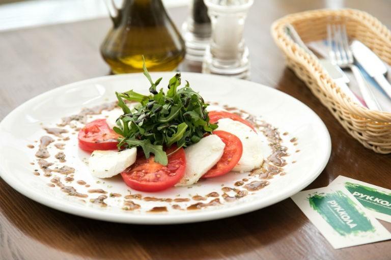 салат Капрезе с соусом и зеленью на белой широкой тарелке на столе
