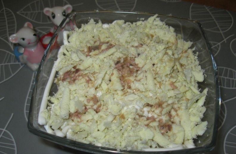слоеный салат из тертых яичных желтков и майонеза в стеклянной миске на столе