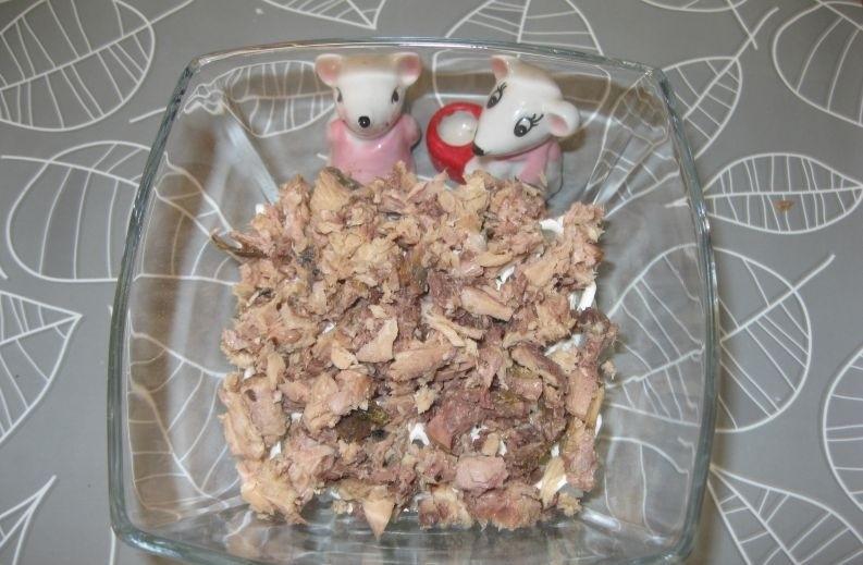слоеный салат из кусочков консервированного тунца в стеклянной миске на столе