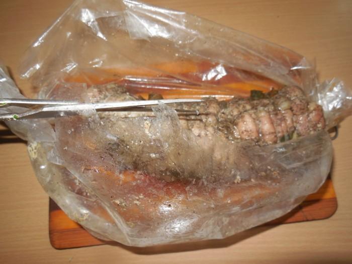 вареный рулет из сала в разрезанном пакете для запекания на полосатой деревянной разделочной доске на столе