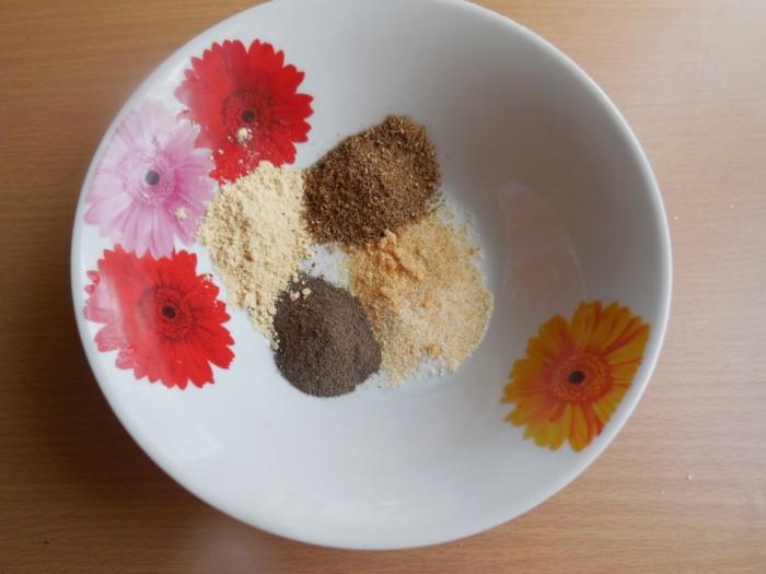разные горки со специями в глубокой тарелке на столе