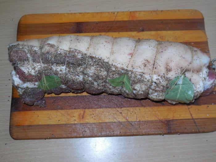 кусок свиного сала, посыпанный специями и свернутый рулетом с лавровыми листиками, перевязанный нитками, на полосатой деревянной разделочной доске на столе