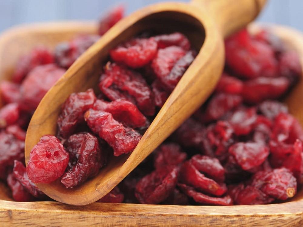 сушеная вишня в деревянной лопатке и миске