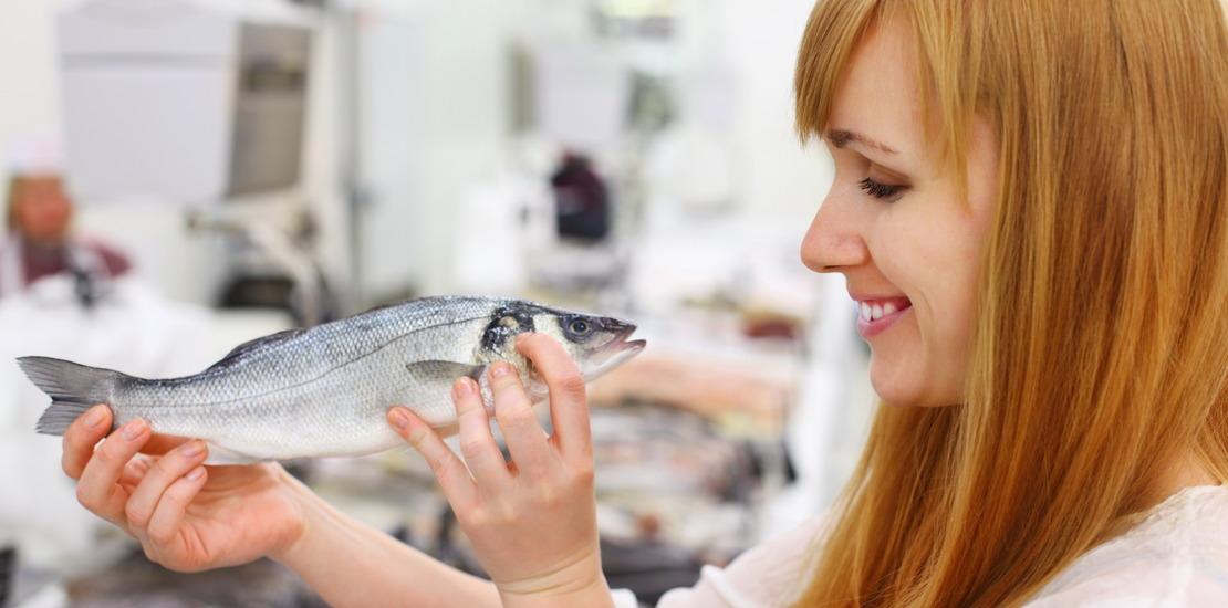 женщина держит в руках рыбу