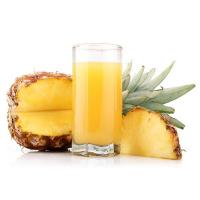 стакан ананасового сока и разрезанный ананас рядом