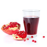 гранатовый сок в стакане, рядом разрезанный плод граната