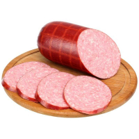 треть палочки копченой колбасы на круглой деревянной доске для разделки, рядом четыре отрезанных ломтика колбасы