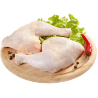 свежие куриные окорочка на деревянной подставке с зеленью