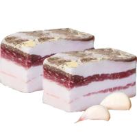 кусочки свиного сала с чесноком на белом фоне