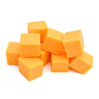 фото чеддера, нарезанного кубиками, на белом фоне