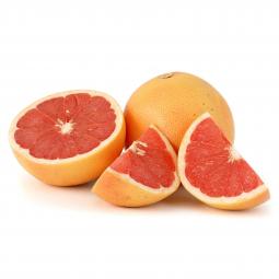 фото разрезанного на дольки грепфрута, рядом лежит целый фрукт