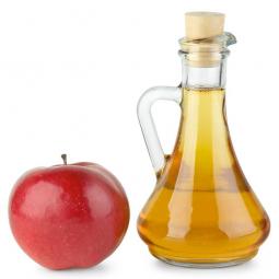 бутылка яблочного уксуса и яблоко на белом фоне