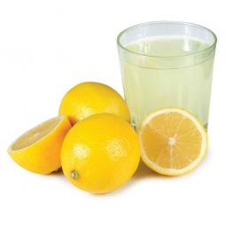 стакан лимонного сока, целые и разрезанные лимоны рядом