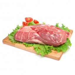 фото свиной шеи, которая лежит на деревянной доске на листьях салата, рядом свежие помидоры