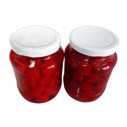 фото двух банок вишен в сахарном сиропе на белом фоне