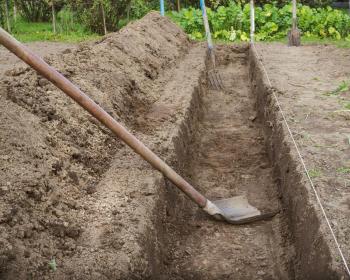 вырытая траншея и лопата