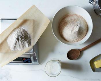 мука на весах и в миске на столе, рядом деревянная ложка и кусок сливочного масла