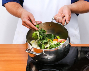 пучок зелени, лук, помидоры в кастрюле на плите