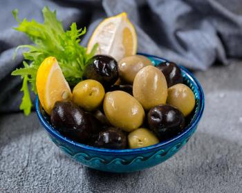 оливки и маслины в синей тарелке