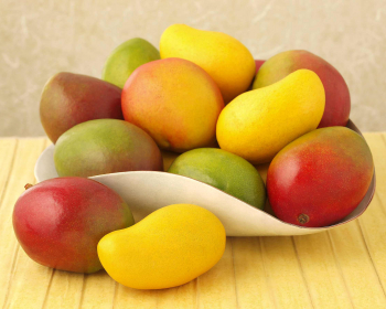 спелое манго на тарелке на столе